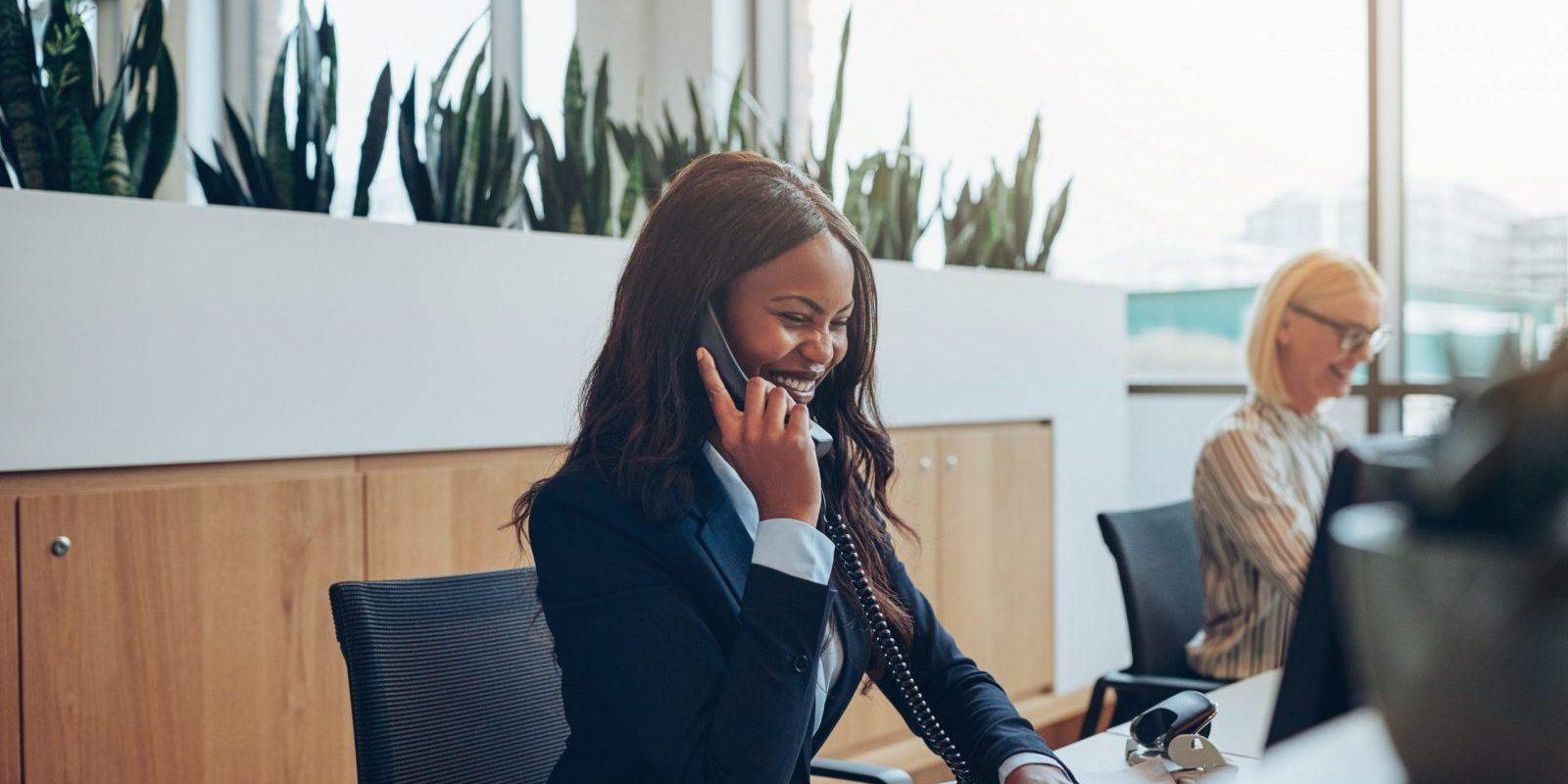 Young African American businesswoman laughing while talking on a telephone and working on a computer at an office reception